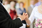 Bride putting a wedding ring on groom's finger — Stock Photo