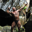 Stock Photo: Young bodybuilder posing in a cave - front view in full length p