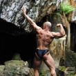 Bodybuilder posing in a cave - back view - Stock Photo