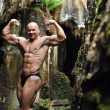 Young bodybuilder posing in a cave - Perfect body — Stock Photo