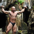 Bodybuilder posing in a cave — Stock Photo