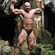 Royalty-Free Stock Photo: Young bodybuilder posing in a cave - Front view