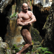 Royalty-Free Stock Photo: Young bodybuilder posing in a cave - Full length portrait