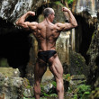 Young bodybuilder posing in a cave - latissimus dorsi — Stock Photo