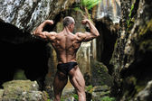 Bodybuilder posing in a cave - posterior back muscles — Stock Photo