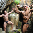Bodybuilder posing behind another bodybuilder in the blurring - Stock Photo