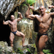 Stock Photo: Bodybuilder posing after another bodybuilder in the blurring