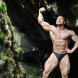 Young bodybuilder posing in a cave — Stock Photo