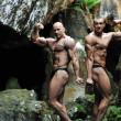 Two young bodybuilders posing in a cave — Stock Photo