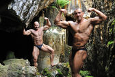 Bodybuilder posing after another bodybuilder in the blurring — Stock Photo