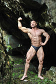 Young bodybuilder posing in a cave - Front view — Stock Photo