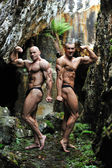Two bodybuilders posing in a cave - Full length portrait — Stock Photo