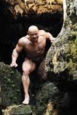 Homem musculoso sobe fora da caverna — Fotografia Stock