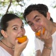 Young couple eating fresh orange — Stock Photo
