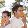 Young couple eating fresh orange — Stock Photo #10542858