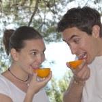 Young couple licking fresh orange — Stock Photo #10542864