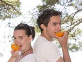 Young couple eating fresh orange — Stock Photo