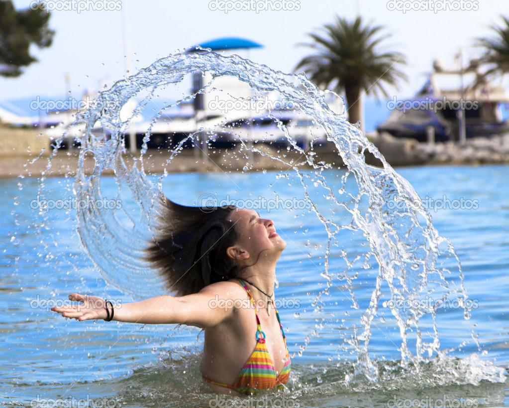 Cute young girl splashing out of the water on the beach — Stock Photo #10542526