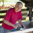Foto Stock: Happy smilling carpenter with power plane tool
