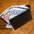 Royalty-Free Stock Photo: Euros in  black leather wallet, on vintage brown background