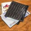Royalty-Free Stock Photo: Euros with joker and casino members card in black leather wallet, on vintag