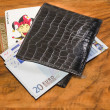 Euros with joker and casino members card in black leather wallet, on vintag — Stock Photo