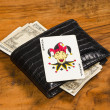 Royalty-Free Stock Photo: Dollars with joker card on closed wallet, on vintage brown background