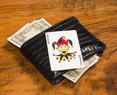 Долларов с карты джокера на закрытые карманы, на фоне старинных коричневый — Стоковое фото