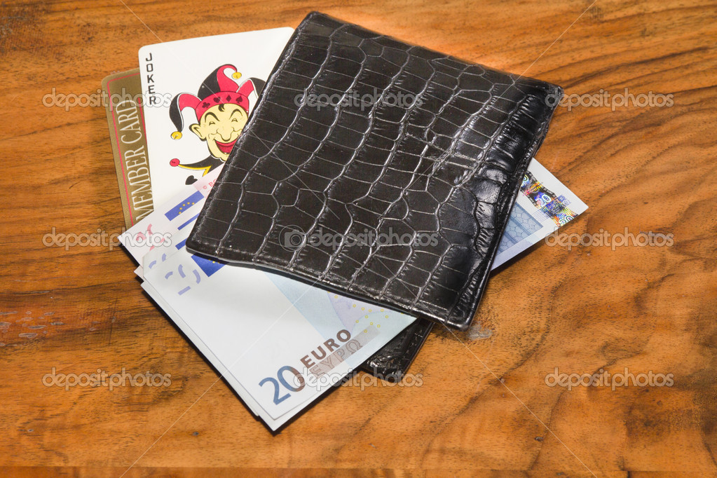 Euros with joker and casino members card in black leather wallet, on vintage brown background — Stock Photo #9123516