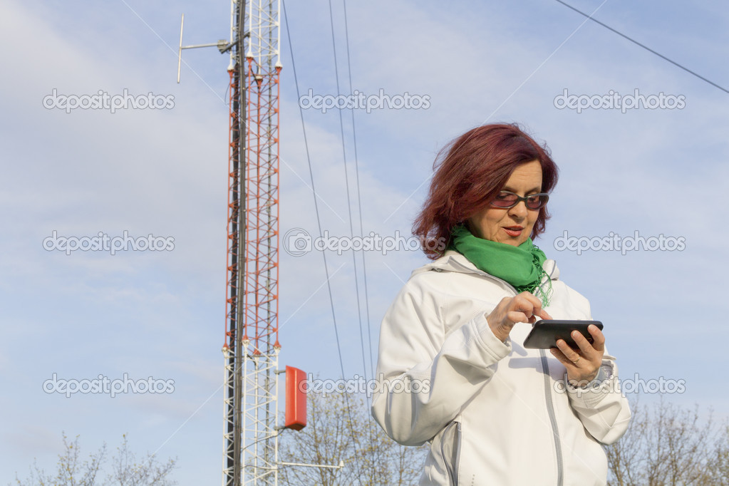 Good looking mid age woman with tablet phone under big antenna tower  Stock Photo #9885260
