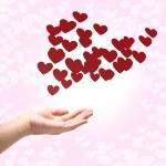 många röda hjärtan på hand, rosa bakgrund — Stockfoto