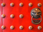 Red chinese door with a lion/dragon head. — Stock Photo