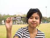 Girl trying her glasses and checking out their dirtiness — Stock Photo
