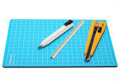 Cutter,pencil and Scale placed on blue cutting mat. — Stock Photo