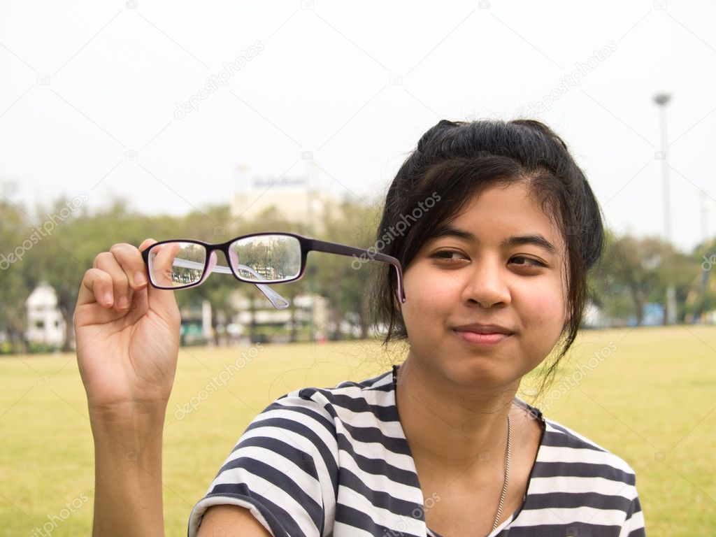 Girl trying her glasses and checking out their dirtiness — Stock Photo #9774418