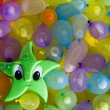 Toy star between colored ballons — Stock Photo