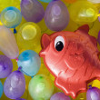 Red toy fish between colored ballons — Stock Photo