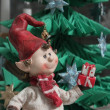 Stock Photo: Christmas elf giving present under christmas tree