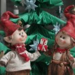Christmas elfs boy and girl giving a present under christmas tre — Stock Photo