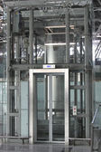 Big glass luggage elevator in the airportr — Stock Photo