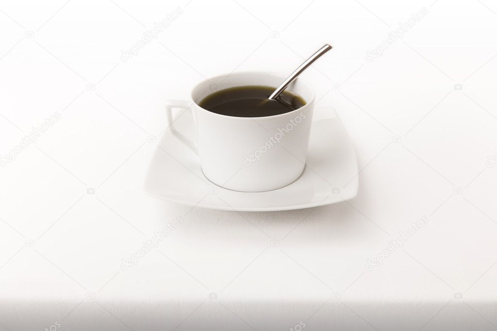 A modern cup of tea with a spoon on a white tablecloth with real shadow bottom — Stock Photo #9028472