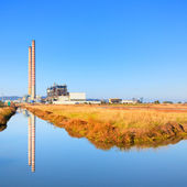 Power plant with smoke stacks and reflection on water — Стоковое фото