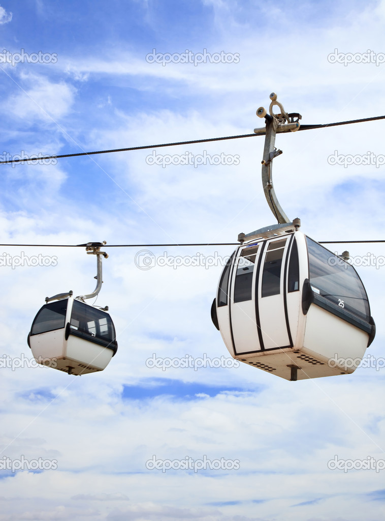 A cablaway with two cable car on a partly cloudy blue sky background — Stock Photo #9632077