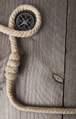 Old compass, rope and on wooden background — Stock Photo