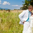 Bride and groom hugging at green field — Stock Photo