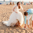 Bride and groom at the crowded beach — Foto de Stock