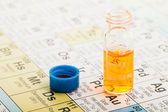 Chemistry: Periodic table and vial — Stock Photo