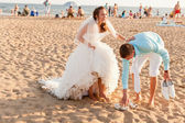 Bride and groom at the crowded beach — Stock Photo