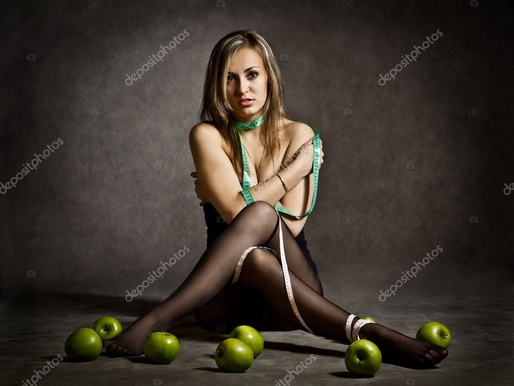 A sad pretty young blondie topless with a fear on her face wound herself with a centimeter measurement tape sitting at the floor in front of some green apples — Stock Photo #8876691