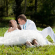 Bride and groom huggling sitting at green grass — Stock Photo #9310966
